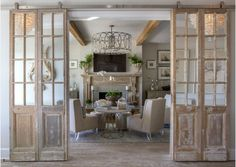 Shingle Style Gambrel Beach House Mirrored antique doors were hung in a barn door hardware in the formal living room to bring character and patina. The pale pine vintage mirror door set also features a whitewashed finish. Antique Doors, Old Doors, Antique Mantel, Sliding Doors, Old French Doors, Entry Doors, Interior Double French Doors, Salvaged Doors, Pine Doors