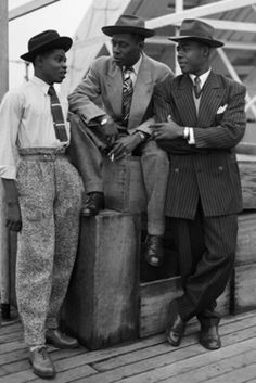 Three Jamaican immigrants,(left to right) John Hazel, a 21-year-old boxer, Harold Wilmot, 32, and John Richards, a 22-year-old carpenter, arriving at Tilbury Docks, Essex on board the ex-troopship SS Empire Windrush on 22 June 1948, smartly dressed in 'Zoot Suits' and trilby hats. The Edwardian Teddy Boy - British Teddy Boy History