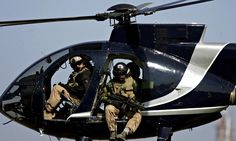 Blackwater private security guards scan Baghdad from their helicopter.  Photograph: Marwan Naamani/AFP/Getty Images