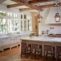 Love all the natural light, the rustic beams, the light fixtures, textures, white cabinets