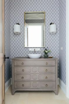 Chic powder room features walls clad in blue Arabesque Scalloped Wallpaper lined with a gray dresser turned washstand adorned with brass ring pulls topped with a bowl sink placed under a wall mount faucet and a metal framed mirror lit by drum shade wall sconces.
