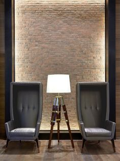 backlit brick wall, architect's lamp and matching high-backed chairs. Interior Desing, Interior Inspiration, Interior Architecture, Interior Decorating, Arch Light, Architect Lamp, Hospitality Design, Commercial Design, Unique Furniture
