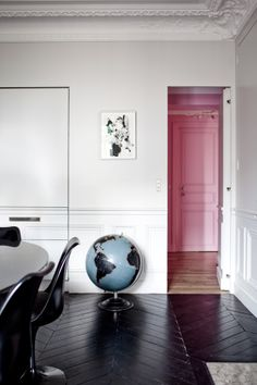 Playful color blocking, pink door, black chevron wood floors