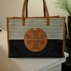 """Authentic Tory Burch Bag 13x9"""" Gently used with some signs of wear. Navy and tan color. Carry all type tote.  Structured and sturdy. One of the shoulder straps had to be professionaly restiched from wear.The upper part of the straps are darker in color from wear. Original tag included. Tory Burch Bags Totes"""