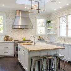 I wouldn't be sad if my kitchen looked like this. Could be done pretty cheaply via some white paint, some Ikea butcher block slab tops, and some metal bar stools and cabinet hardware from Overstock.com (both which you can spraypaint whatever color you want)