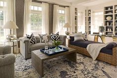 Living room. Transitional living room features walls clad in grey textured wallpaper framing windows dressed in soft white drapes alongside a gray tufted sofa with brass nailhead trim adorned with black and white pillows flanked by round glass top end tables and mercury glass lamps facing a rippled waterfall coffee table atop a blue and gray paint splatter rug. #LivingRoom #TransitionalLivingRoom HB Home.