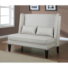 Offering a contemporary look and featuring lovely linen upholstery, this wing back loveseat comes complete with a pair of lumbar support pillows. Featuring sturdy wood legs, it is embellished with stylish nailhead trim and welt cord.