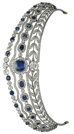 Large image A BELLE EPOQUE SAPPHIRE AND DIAMOND TIARA The base designed as an openwork wreath of diamond-set laurel leaves, centering upon a circular-cut diamond collet, surmounted by a series of graduated cushion-shaped sapphires in diamond-set clusters, a diamond-set wavy line and alternated diamond and sapphire collets on top, Carrington and Co, about 1910. Image Christies