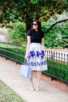 Navy blue geometric eyelet top, white midi skirt with blue floral print, light blue strappy heels, and light blue bag