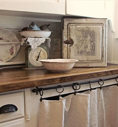 curtain (cotton?) on rings & curtain rod. wood countertop.platter holder against backsplash. remove the bothersome doors under the sink, replace with curtains. install wood countertops from Ikea & stain, age, apply wax seal. the perfect update.
