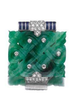 JADEITE, ENAMEL AND DIAMOND CLIP, CARTIER, PARIS, 1930S The open work carved jadeite plaque inset with single-cut diamonds, highlighted with blue translucent enamel, signed Cartier and numbered, French assay and partial maker's marks.