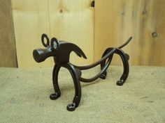 Weiner dog that I made out of Horseshoes and round bar steel, plus some nuts, washers and an old hammer head.: