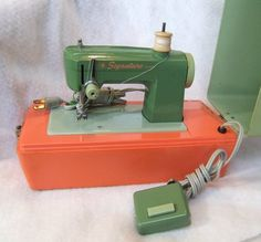 A terrific little vintage Montgomery Ward Signature Junior electric sewing machine. Circa mid to late 1970s. Green and orange colors are vibrant, attached heavy duty plastic carrying case. Machine is 7 inches long and 3.5 inches high, made of metal with a hard plastic base and cover.