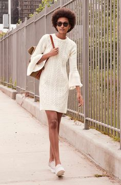 Statement-making ruffled cuffs add an on-trend finish to this classically cabled sweater-dress stitched from soft, cozy yarns.