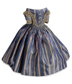 """To fit lady doll about 18"""". 4"""" shoulders. Of slate-blue silk with interwoven coral and cream stripes,the gown features a low-shouldered bodice with center panel of ruching,elbow-length sleeves,V-shaped waist above a full skirt with cartridge pleating at the waist; with bands of loosely-woven braid trimming the bodice and sleeves. Excellent condition. Circa 1860."""