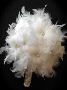 Weddbook ♥ This white feather snow flake bridal bouquet forms a perfect combination with your traditional white wedding dress. The base and center of the feather flowers of the bouquet is embellished with shining silver crystals which makes it look amazing and stylish.