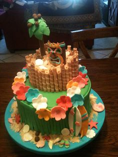 """By K. Andrews: Aloha! Hawaiian Luau cake! Seashells, surfboards, lei flowers, tiki face, tree, etc. are made of fondant (before I discovered gumpaste). Cake base is covered in turquoise fondant to look like water and """"sand"""" is made from graham crackers."""