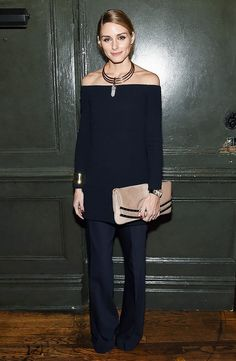 Olivia Palermo wears an off-the-shoulder tunic, wide-leg pants, a clutch, and statement jewelry