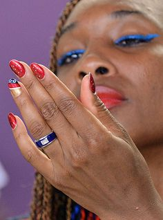 US tennis player Venus Williams looks at her hand as her fingernails are adorned with US national colors during a press conference before the start of the London 2012 Olympic Games Photograph: Jewel Samad/AFP/Getty Images