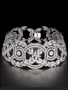"""EXQUISITE ANTIQUE DIAMOND 'ELISE' CHOKER CIRCA 1900. Of openwork foliage scroll design, set with intertwining wreaths of diamond-set laurel leaves, accented by six oscillating old-cut diamonds. Mounted in platinum. This exceptional vintage necklace was found by Robert Procop, particularly for the character """"Elise Clifton-Ward"""" portrayed by Angelina Jolie in the film The Tourist in 2010."""