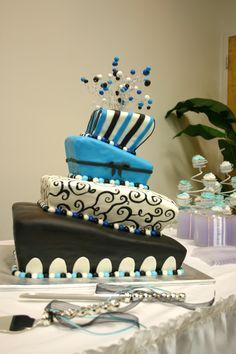 Square topsy-turvy style wedding cake in blue, black and white featuring hand-painted scroll work, stripes and fondant cut-outs.