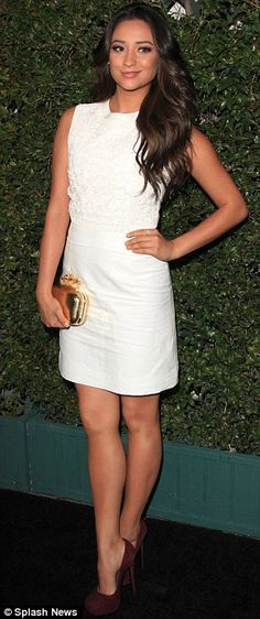 Shay Mitchell in white with red shoes and a gold clutch.