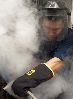 Machinist's Mate 2nd Class Thao Tran tests liquid nitrogen in a cryogenic plant aboard the Nimitz-class aircraft carrier USS Abraham Lincoln (CVN 72).