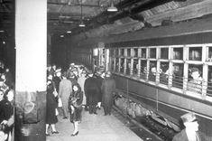Crowds board commuter trains at City Hall station during WWII (circa 1944).