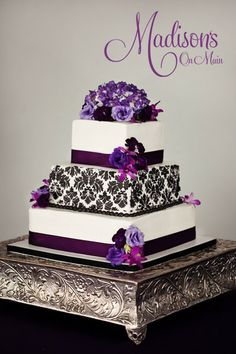 I created this wedding cake in buttercream with a black buttercream damask stencil on the middle tier. Plum ribbon and fresh flowers accent the tiers. donnaok