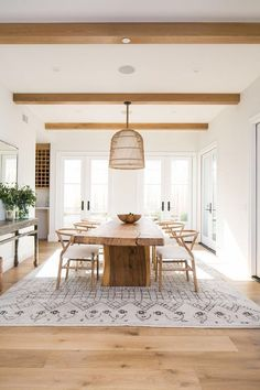 Modern minimal dining room with basket woven chandelier, live edge table, wishbone chairs, Mororccan Rug, All white room with wood ceiling beams