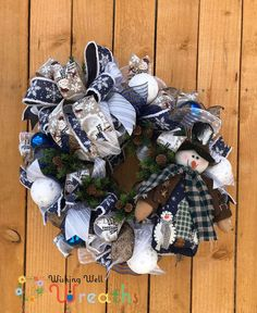 This fun Blue Christmas Snowman Wreath is perfect for anyone who loves that Country Farmhouse feel! This snowman wreath is covered in shiny blue mesh with silver threads running throughout it. An adorable winter country looking snowman doll rests on the corner of the wreath, Opposite the snowman is a giant bow with beautiful ribbons the ribbons include a snowy snowflake design, a fun brown snowman print, and a white and silver glittered pattern!