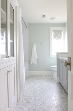 The pale neutral colors create a spa atmosphere in this bathroom. The shaker cabinet fronts and Carrera style hexagonal flooring provide some old world charm
