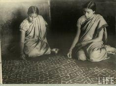 Two ladies creating Alpana (Rangoli) on the floor