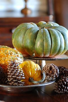 thanksgiving decor...love the off-shades of pumpkins and the pine cones mixed in.