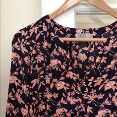 """Dalia Blouse Sweet floral blouse in excellent condition. Can be dressed up or down. V-neck without buttons. Cuff has a button. 27"""" shoulder to hem.  Beautiful floral print in pink, tan and navy. 100% polyester. Dalia Tops Blouses"""