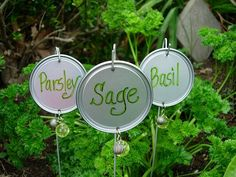 Homemade garden markers using wire hangers, canning lids or orange juice lids and beads. So cute!!