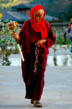 Bhutan very religious people. Woman with prayer wheel.