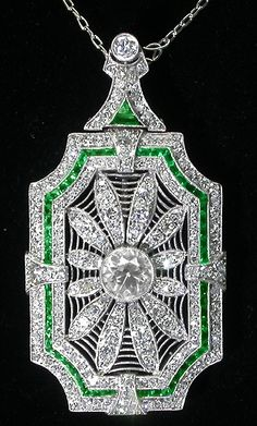 Art Deco 5ct Diamond and Emerald Platinum Pin / Pendant Necklace. The chain is attached to a detachable connector, which when taken out, becomes a pin, via Israel Rose.