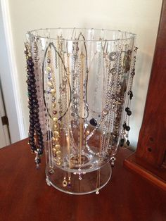 Made this for my wife to hang her necklaces in our new house, Large glass vase, and we used jewelry wire to make small hooks that hang over the lip of the vase and allow you to hang a necklace on both sides. Very simple and very cheap solution.