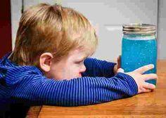 enfant qui regarde un bocal rempli de paillettes