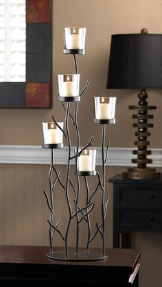 This fantastic candleholder is the perfect blend of contemporary design, natural inspiration, and shimmering candlelight. Five clear glass candlecups sit perched upon iron branches for a dramatic disp
