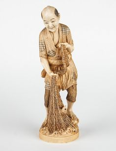 Japanese carved ivory fisherman modeled as man bringing in net of fish, ink highlights, signed in characters underneath, 7 1/2 in. H.