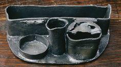 Cette écritoire, faite d'un alliage à forte teneur en plomb, comprend un support à plume, un encrier ou cornet, un sablier ou porte-sablier destiné à contenir la poudre pour assécher l'encre, et une boîte rectangulaire où l'on gardait un canif, un sceau, la cire à cacheter, etc. Il a été découvert dans un contexte archéologique du XVIIe siècle, sur le site patrimonial de l'Habitation-Samuel-De Champlain. Photo : Marc-André Grenier 1998 © Ministère de la Culture et des Communications