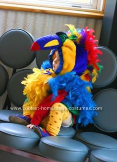 Homemade Parrot Bird Costume Design: I wanted something with tons and tons of feathers. While I was at the thrift store one day, I found a shell for a bird costume. I went to Hobby Lobby and