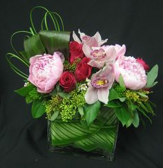This is a cube vase floral arrangement that features roses, peonies and cymbidium orchids in different shades of pink with green accents.  See our entire selection at www.starflor.com.  To purchase any of our floral selections, as gifts or décor, please call us at 800.520.8999 or visit our e-commerce portal at www.Starbrightnyc.com. This composition of flowers is generally available for same day delivery in New York City (NYC). SQ228