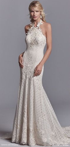Embroidered lace motifs cascade over allover lace in this unique wedding dress, accenting the bust, fit-and-flare skirt, and breathtaking train. Lace motifs create a halter neckline that ties over the open back. Lined with Viva Jersey for a luxe fit. Finished with zipper closure.