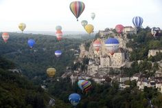 Google+   Hot air balloons fly over the French clifftop medieval town of Rocamadour during the Rocamadour Hot Air Balloon Festival on September 26, 2015