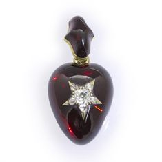 A Victorian heart-shaped garnet and diamond pendant, the cabochon-cut garnet with a diamond-set star motif applied to the centre, the old brilliant-cut diamond estimated 0.30 carats all to a yellow gold mount with glass locket at the back and cabochon-cut garnet-set pendant loop, circa 1860.