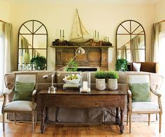 dinged up table, sagging ever so slightly in the middle, finds a newfound sense of dignity when flanked by a pair of reproduction French armchairs in this living room. Old metal window frames retrofitted with gleaming mirrors