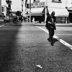 In downtown LA, a man counts his change as he crosses 6th street. @americanobscura for @streetvogs